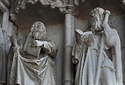 2 statues holding books under canopies flanking the doors, on the South Portal, 1516-18, by Joao de Castilho, 1470ñ1552, after a design by Diogo de Boitaca, Church of Santa Maria, at the Jeronimos Monastery or Hieronymites Monastery, a monastery of the Order of St Jerome, built in the 16th century in Late Gothic Manueline style, Belem, Lisbon, Portugal. The portal consists of double doors with a tympanum carved with scenes from the life of St Jerome, a statue of Henry the Navigator, many carved statues in niches, a statue of the Madonna and many flamboyant pinnacles and gables in Manueline style. The monastery is listed as a UNESCO World Heritage Site. Picture by Manuel Cohen