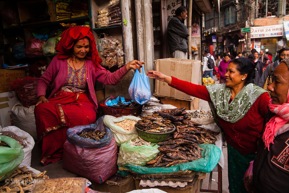 Women enjoying selling and buying dried fish at the oldest open air market in the Thamel District in Kathmandu, Nepal.