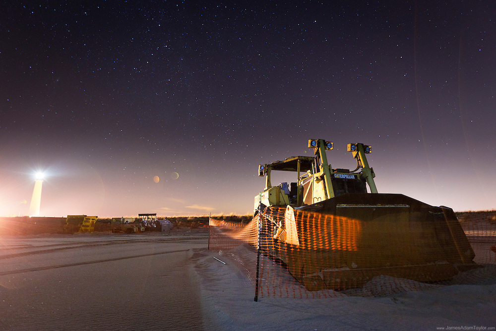The beach and heavy equipment illuminated by the Cape May Lighthouse.
