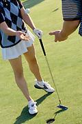 Female golfer tossing golf ball to male golfing partner on golf green.