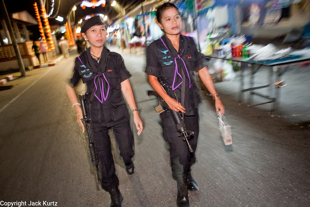 Sept. 29, 2009 -- YARANG, THAILAND: Members of the women's Ranger unit walks through the night market in Yarang, Thailand, during a security sweep, Sept. 29. The 39 women in the 44th Army Ranger Regiment are the only Thai women seeing front line active duty against Moslem insurgents in Thailand's deep south provinces of Pattani, Narathiwat and Yala. All of the other women serving in Thai security services are employed as office and clerical workers. The Ranger women are based at the Ranger camp in the Buddhist village of Baan Trokbon in Sai Buri district of Pattani province. The unit was formed in 2006 after Muslims complained about the way Thai soldiers, all men, treated Muslim women at roadblocks and during security sweeps. The women are frequently called upon to back up Thai regular army units when they are expected to encounter a large number of Muslim women. At least two of the women have been killed by Muslim insurgents. The unit has both Muslim and Buddhist members. Many of the women in the unit joined after either their fathers or husbands were killed by insurgents.  Photo by Jack Kurtz / ZUMA Press