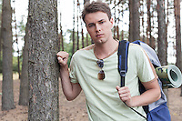 Portrait of handsome young man with backpack hiking in forest