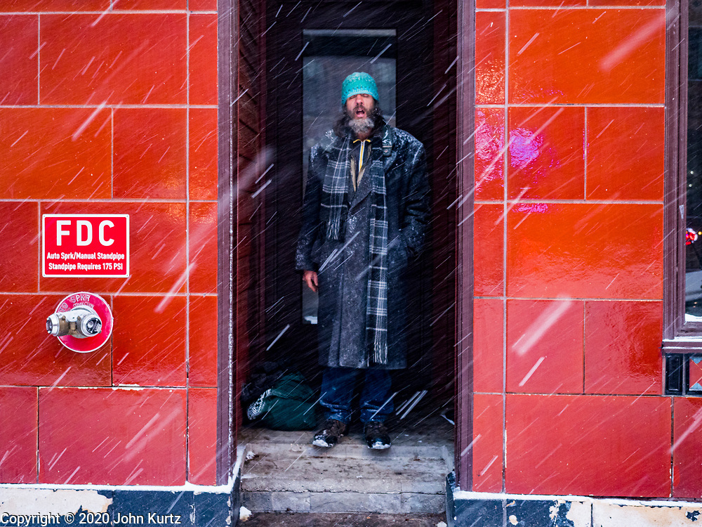10 JANUARY 2020 - DES MOINES, IOWA: A man takes shelter in the doorway of a building in downtown Des Moines during a snowstorm Friday. The first significant snow in two months blanketed Des Moines Friday evening. Meteorologists are predicting up to six inches of snow overnight and have issued a winter storm warning for southern and central Iowa. Most schools in the affected area closed early and cancelled afternoon events. Some presidential candidates, campaigning ahead of the Iowa Caucuses, cancelled their events.      PHOTO BY JACK KURTZ