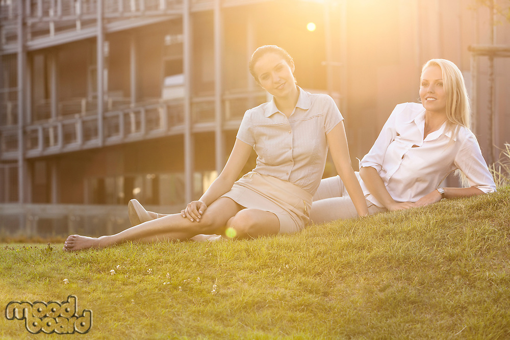 Beautiful young businesswomen relaxing on office lawn