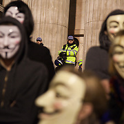 Masked up members of Anonymous in front of the cathedral being wathed by police further up the steps.The London Stock Exchange was attempted occypied in solidarity with Occupy Wall in Street in New York and in protest againts the economic climate, blamed by many on the banks. Police managed to keep people away fro the Patornoster Sqaure and the Stcok Exchange and thousands of protestors stayid in St. Paul's Square, outside St Paul's Cathedral. Many camped getting ready to spend the night in the square.