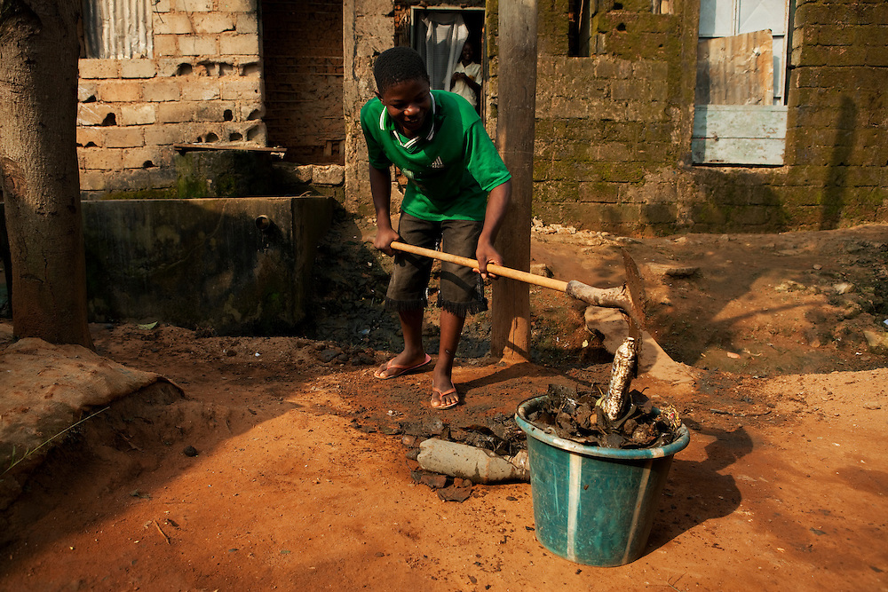 A boy cleans the gutter in front of his house from garbage.  Mokolo, Yaounde, Cameroon.