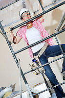 Front view of female worker climbing on scaffold