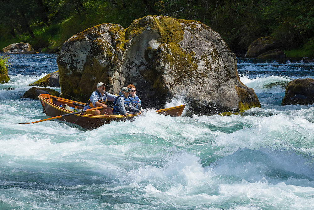 Guide Greg Hatten takes guest on his wooden drift boat through Marten Rapids on the McKenzie River, Oregon.
