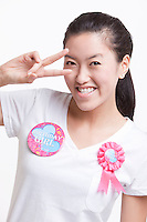 Portrait of Asian woman gesturing peace sign against white background