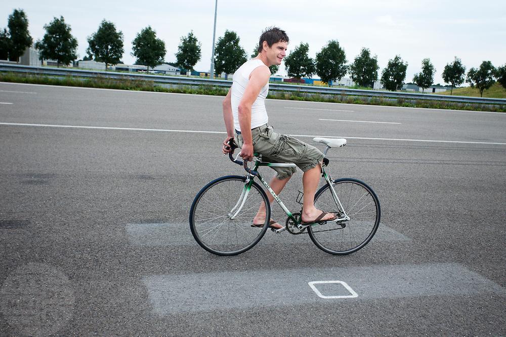 Jan Bos doet een kunstje op een racefiets. Het Human Power Team Delft en Amsterdam (HPT) traint op de RDW baan in Lelystad met de VeloX2 voor de recordpoging in september. Het HPT hoopt dan in Amerika meer dan 133 km/h te rijden over 200 meter.<br /> <br /> Jan Bos does some tricks on a racing bike. Human Powered Team Delft and Amsterdam (HPT) is training at the RDW test track in Lelystad with the VeloX2 for the record attempt in september.