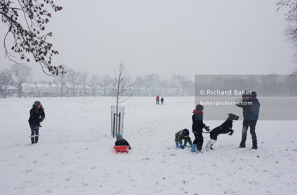 A family out in the snow enjoy a winter's day with their pet dog in a snowbound south London park.