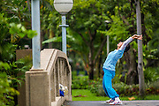 06 OCTOBER 2012 - BANGKOK, THAILAND:  A woman stretches while exercising in Lumphini Park in Bangkok. The Thai government promotes exercise classes as a way staying healthy. Lumphini Park is 142 acre (57.6-hectare) park in Bangkok, Thailand. This park offers rare open public space, trees and playgrounds in the congested Thai capital. It contains an artificial lake where visitors can rent boats. Exercise classes and exercise clubs meet in the park for early morning workouts and paths around the park totalling approximately 1.55 miles (2.5 km) in length are a popular area for joggers. Cycling is only permitted during the day between the times of 5am to 3pm. Smoking is banned throughout smoking ban the park. The park was created in the 1920's and named after Lumbini, the birthplace of the Buddha in Nepal.   PHOTO BY JACK KURTZ