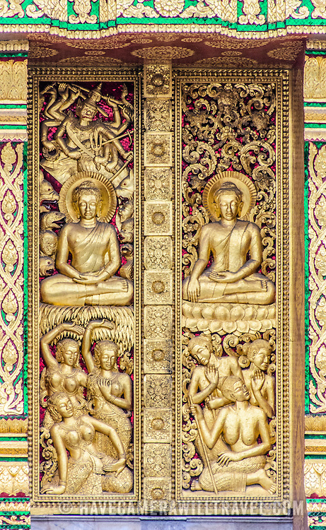 The ornately decorated gold-leaf door of a wat (Buddhist Temple) in Luang Prabang, Laos. The depiction is of the Gods (above) and humans (below).
