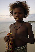 Child selling necklaces on the beach made from seeds and shells found locally.<br />