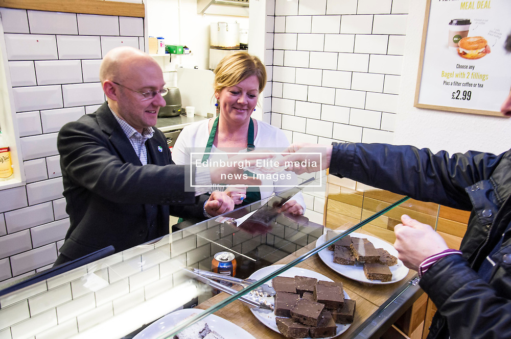 Pictured: Bonnie Burton watches carefully as Patrick Harvie makes a sale<br /> <br /> Greens co-cordinator Partrick Harvie headed to Rose Street in Edinburgh today to serve customers at Social Bite cafe, a social enterprise supporting the homeless<br /> <br /> Ger Harley | EEm 20 April 2016