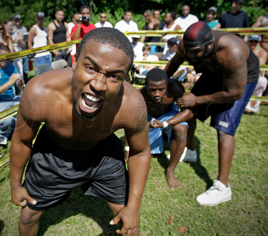 "Charles Woodard, left, revels in defeating Alfonso ""Chocolate"" Frierson on September 18, 2010. At right is Dhafir Harris, ""Dada 5000"". .Dada 5000 puts on backyard fights at his mother house, which go viral on youtube and have been the subject of documentaries. Sometimes the men fight until they are unconscious. There' s no gloves and occasionally, there's a cage. The community has taken to the events, because they are able to set up businesses selling food and washing cars."