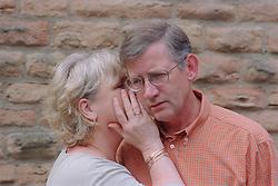 Woman whispering in man's ear,