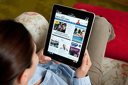 Woman using iPad tablet computer at home to read The Sunday Times  UK newspaper