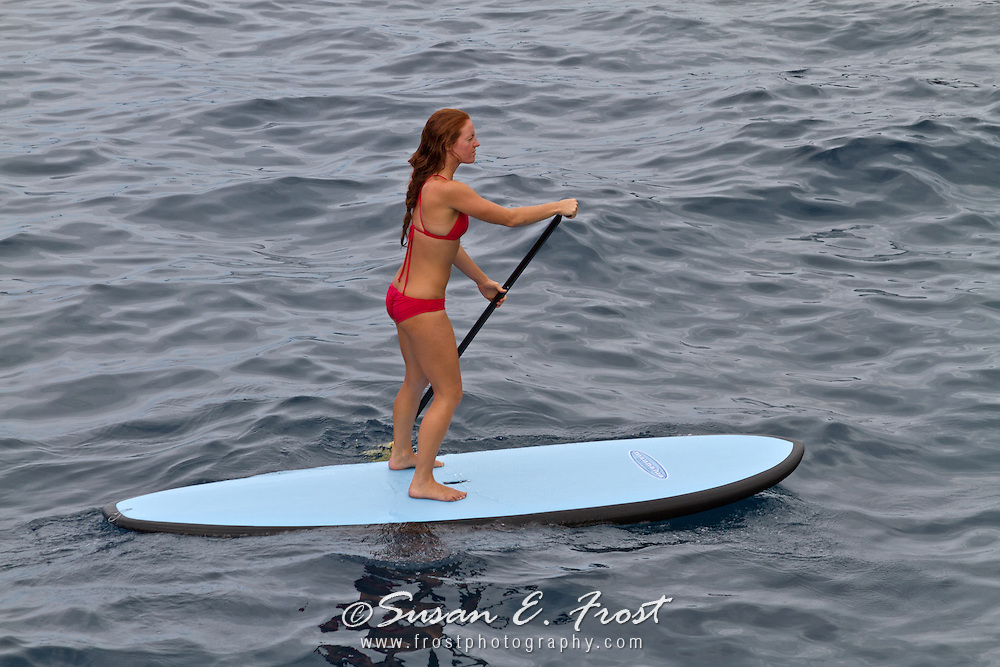 Bikini clad woman demonstrating stand up paddling in the tropical waters of Big Island Hawaii.