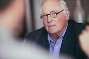 Elderly man discussing finance in a corporate meeting.