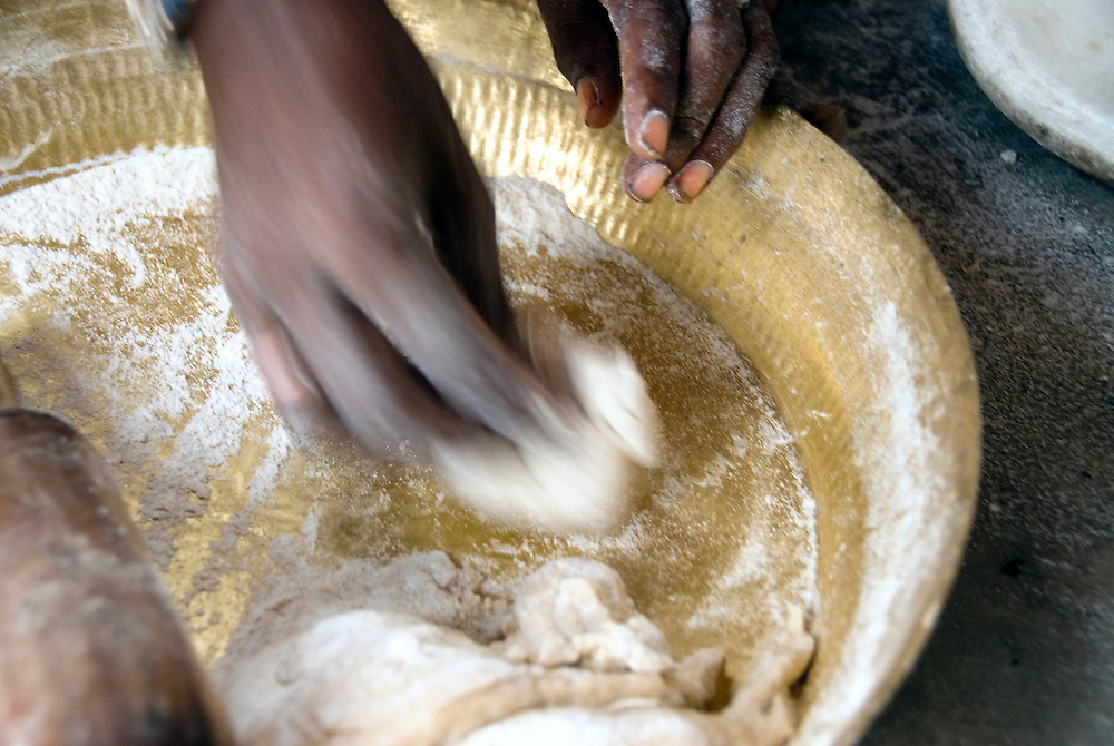 Detail of the woman's hand preparing roti (bread) for dinner.