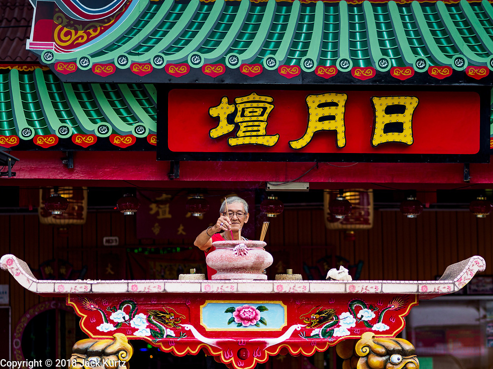 26 AUGUST 2018 - GEORGE TOWN, PENANG, MALAYSIA: A man prays at the temple on the Lim Clan Jetty before a Hokkien style opera troupe from China performs on the jetty for the Hungry Ghost Festival. The Hungry Ghost Festival is a traditional Buddhist and Taoist festival held in Chinese communities throughout Asia. The Ghost Festival, also called Ghost Day, is on the 15th night of the seventh month (25 August in 2018). During the Hungry Ghost Festival, the deceased are believed to visit the living. In many Chinese communities, there are Chinese operas and puppet shows and elaborate banquets are staged to appease the ghosts.     PHOTO BY JACK KURTZ