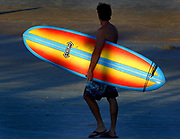 A surfer walks along the shadows near the Daytona Beach, Fla. boardwalk heading for the surf on a nearly deserted beach, Wednesday afternoon, October 19, 2005. (Daytona Beach News-Journal, Craig Litten)<br /> ED NOTE: Color only please-JM
