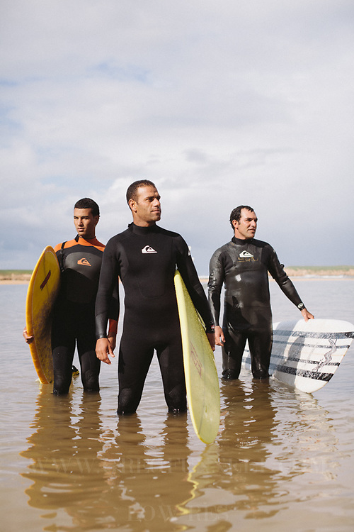L-R; Mehdimir, Chouaib Le Brouj, and Sajid Muhammed pose in the water in Oualidia, Morocco.