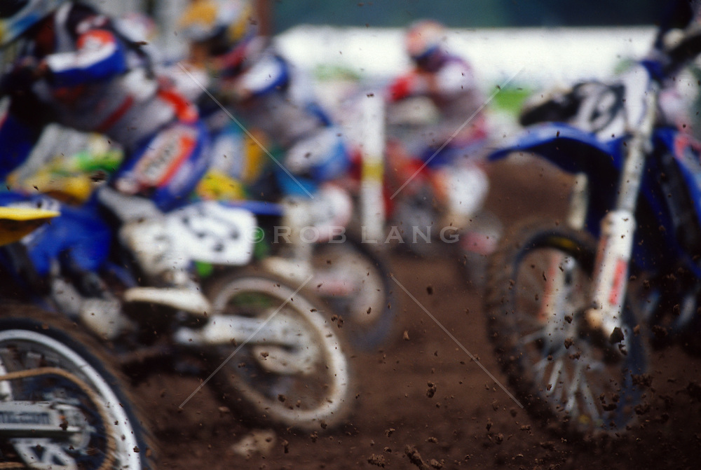 Detail of motor cross bikes and racers on a muddy track