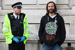 London, UK. 9 October, 2019. Police officers arrest a climate activist from Extinction Rebellion who had locked himself to a fellow activist with an arm tube in order to assist with the blocking of Whitehall on the third day of International Rebellion protests.