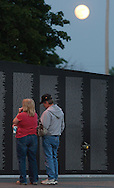 Newburgh, NY - A couple looks at the names on the Vietnam Veterans Memorial Moving wall at Stewart International Airport at the moon rises in the background on June 6, 2009. A yellow rose is taped to the wall at right.