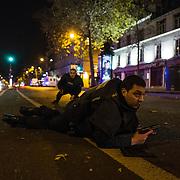Des policiers se mettent à couvert tandis que des individus tirent dans leur direction, le 13 novembre 2015 boulevard des Filles du Calvaire à Paris, à 500 mètres de la salle du Bataclan dans laquelle se déroulait au même moment une attaque terroriste.