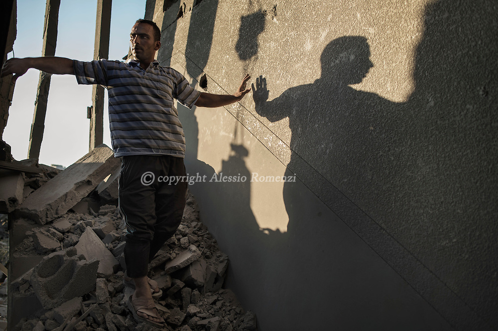 Gaza Strip, Gaza City: A Palestinian man walks on the rubble of his house in Zaitun neighbourhood right after it has been hit by an Israeli airstrike on August 8, 2012. ALESSIO ROMENZI