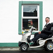 Billy McGowan, a bipolar and polio victim, sits on a mobility scooter parked outside his cottage in Foxford, Co. Mayo.