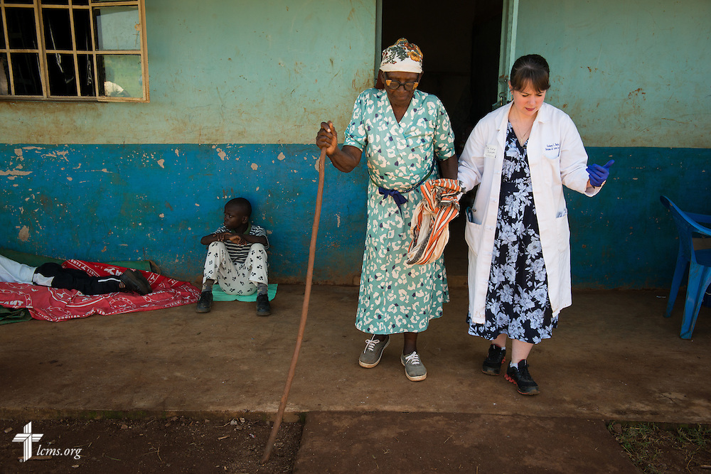 Dr. Katie Butler, a critical care surgeon from Boxford, Mass., attending Our Savior Lutheran Church in Topsfield, Mass., assists an elderly woman during the Mercy Medical Team clinic Tuesday, June 10, 2014, at the Luanda Doho Primary School in Kakmega County, Kenya. LCMS Communications/Erik M. Lunsford