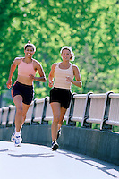 Pair of women jogging together --- Image by © Jim Cummins/CORBIS