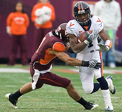 Virginia cornerback Vic Hall (4) is wrapped up by Virginia Tech cornerback Victor Harris (1).  The Virginia Tech Hokies defeated the Virginia Cavaliers 17-14 in NCAA football at Lane Stadium on the campus of Virginia Tech in Blacksburg, VA on November 29, 2008.