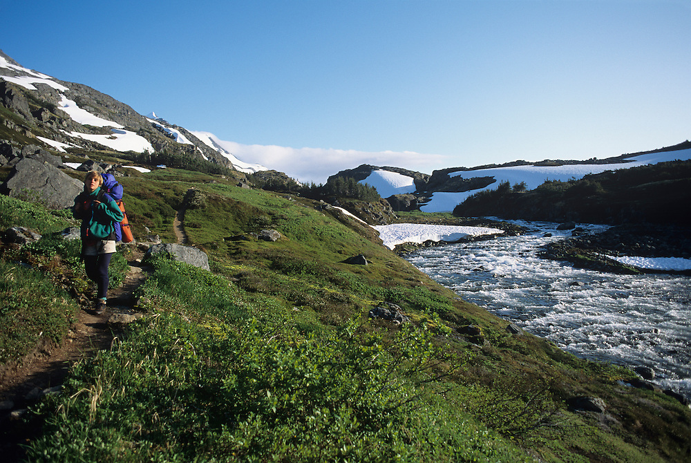 USA, Alaska, (MR) Alyson Pytte hikes along Chilkoot Trail, a 33-mile trail that retraces the 1898 Klondike Gold Rush