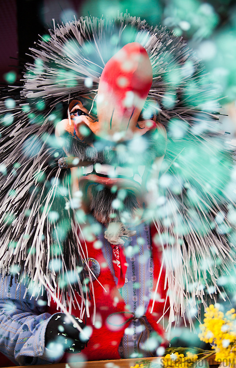 A costumed person throwing confetti into the parade crowd during Carnival (Fastnacht) in Basel, Switzerland.