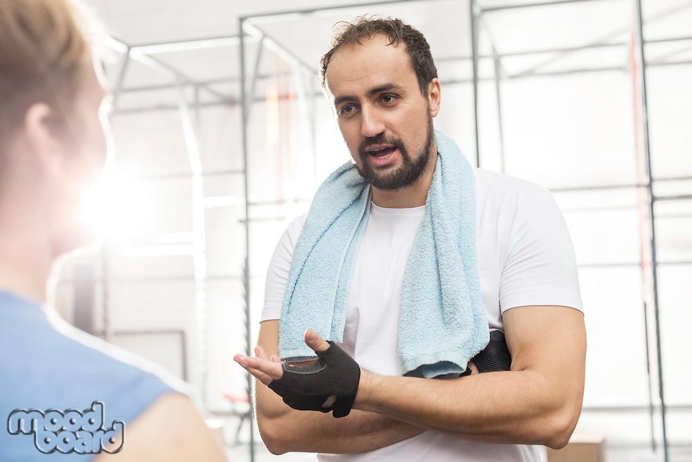 Man talking to male friend in crossfit gym
