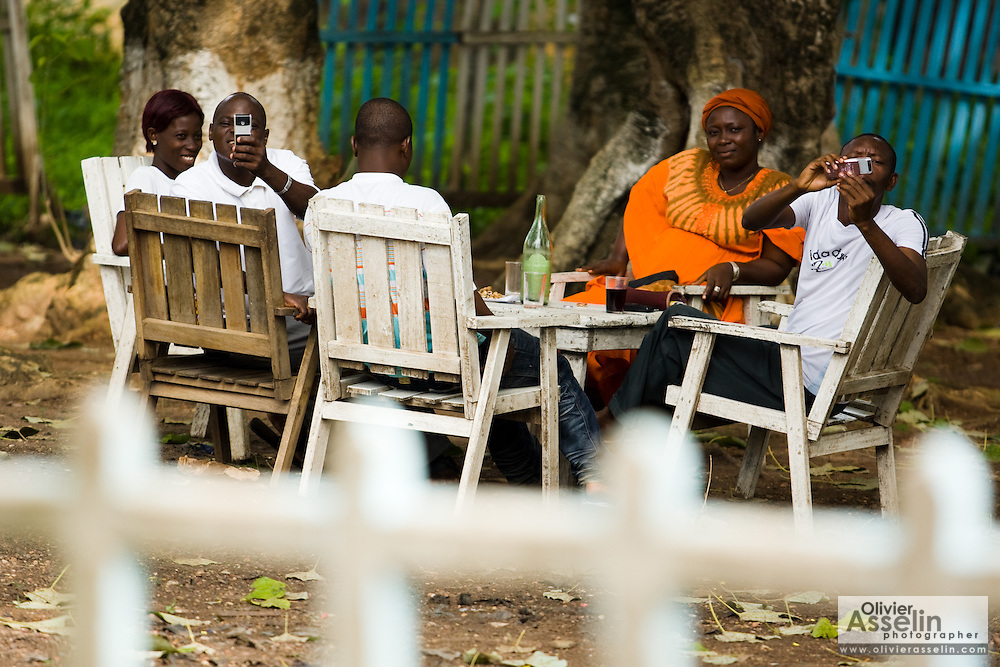 Customers of a local bar take photos of the production crew in Dimbokro, Cote d'Ivoire on Friday June 19, 2009.