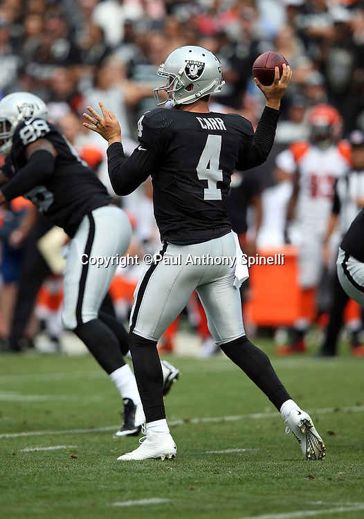 Oakland Raiders quarterback Derek Carr (4) throws a second quarter pass during the 2015 NFL week 1 regular season football game against the Cincinnati Bengals on Sunday, Sept. 13, 2015 in Oakland, Calif. The Bengals won the game 33-13. (©Paul Anthony Spinelli)