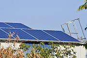 Electricity converting solar panels on a roof of a shed. With the reduction on cost of ownership of these panels, combined with the rise in the cost of electricity have created a positive return on investment on solar electricity. The surplus electricity is sold to the electric company for distribution Photographed in Israel, Arava desert