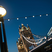 London's famous Tower Bridge at dusk. Constructed in the late 1800s, the ornate Tower Bridge is one of London's iconic landmarks. It gets its name from the nearby Tower of London on the northern bank of the River Thames. In the foreground are lights of Queen's Way, on the southern bank of the Thames.