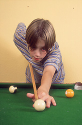 Teenage boy playing pool,