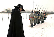 stark--Playing the part of  the town priest, Ted Chatterly, of London, Ontario,  watches re-enactors of His Brittanic Majesty's 41st Regiment of Foot commemorate the 191st anniversary of the Battle of River Raisin at the battlefield in Monroe, Michigan; Saturday, January 17. 2004.  In 1813, British and native troops attacked the small town, then known as Frenchtown, by sneaking up the frozen river.