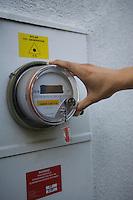 Hand on meter of solar generation unit in Los Angeles California