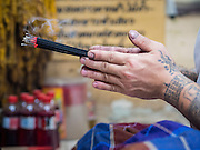 """27 MAY 2015 - BANGKOK, THAILAND:  AJARN NENG ONNUT, a revered tattoo artist in Bangkok, prays at the start of his day of tattooing people in his Bangkok home. Sak Yant (Thai for """"tattoos of mystical drawings"""" sak=tattoo, yantra=mystical drawing) tattoos are popular throughout Thailand, Cambodia, Laos and Myanmar. The tattoos are believed to impart magical powers to the people who have them. People get the tattoos to address specific needs. For example, a business person would get a tattoo to make his business successful, and a soldier would get a tattoo to help him in battle. The tattoos are blessed by monks or people who have magical powers. Ajarn Neng, a revered tattoo master in Bangkok, uses stainless steel needles to tattoo, other tattoo masters use bamboo needles. The tattoos are growing in popularity with tourists, but Thai religious leaders try to discourage tattoo masters from giving tourists tattoos for ornamental reasons.    PHOTO BY JACK KURTZ"""