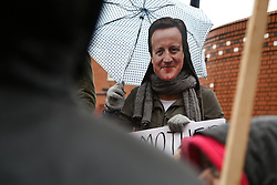 © Licensed to London News Pictures. 09/03/2016. Leeds, UK. An umbrella holding demonstrator wears a David Cameron mask outside Leeds General Infirmary in West Yorkshire at the start of 48-hour walkout by junior doctors. This, the longest strike so far, comes after the government announced it would impose the new contracts upon junior doctors after negotiations broke down.  Photo credit : Ian Hinchliffe/LNP