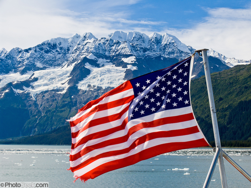 A US flag flies from a boat touring glaciers hanging from the steep and glaciated Chugach Mountains along Harriman Fjord in Prince William Sound, Alaska, USA. Prince William Sound is surrounded by Chugach National Forest (the second largest national forest in the USA). Tour spectacular Prince William Sound by commercial boat from Whittier, which sits strategically on Kenai Peninsula at the head of Passage Canal. Whittier is a port for the Alaska Marine Highway System, a ferry service which operates along the south-central coast, eastern Aleutian Islands, and the Inside Passage of Alaska and British Columbia, Canada. Cruise ships stop at the port of Whittier for passenger connections to Anchorage (by road 60 miles) and to the interior of Alaska via highway and rail (the Denali Express). Known by locals as the Whittier tunnel or the Portage tunnel, the Anton Anderson Memorial Tunnel links Whittier via Portage Glacier Highway to the Seward Highway and Anchorage. At 13,300 feet long (4050 m), it is the longest combined rail and highway tunnel in North America. Whittier was severely damaged by tsunamis triggered by the 1964 Good Friday Earthquake, when thirteen people died from waves reaching 43 feet high (13 meters).